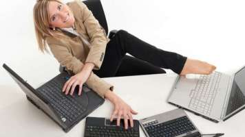 Woman so swamped with work she's trying to use four laptops at once
