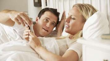 checking smartphone in bed