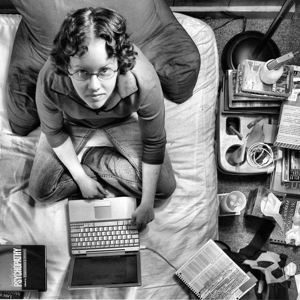 A woman sits on her bed surrounded by books and uses her laptop
