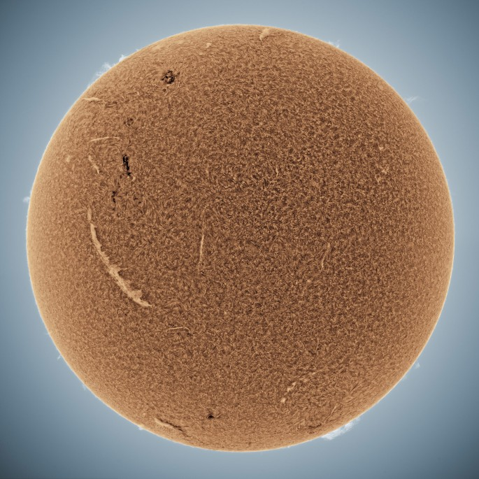 Whole sun pictured in orange with many solar filaments