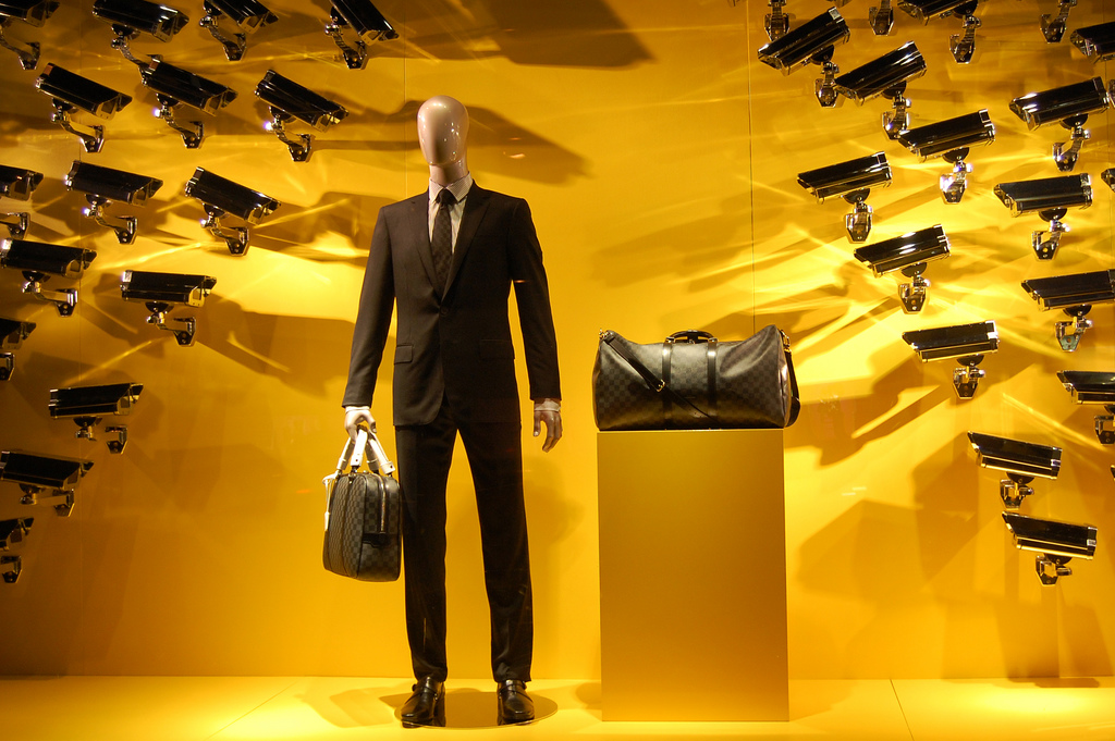 Many video cameras all focus on a male manequin in a suit
