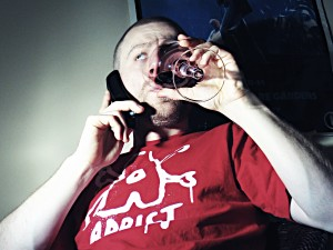 Man In Addict Shirt Drinking Wine While Talking On Phone