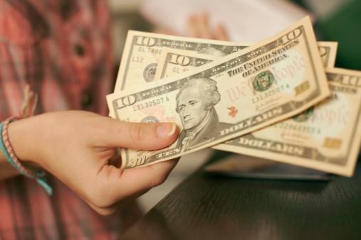 Person holding three ten dollar bills