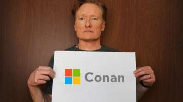 Conan o'brien holds a sign with a redesigned microsoft logo