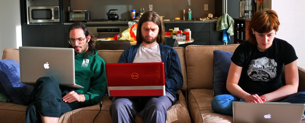 three people sit on couch using laptops