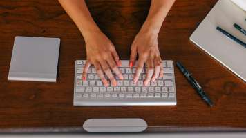 woman with orange fingernails typing